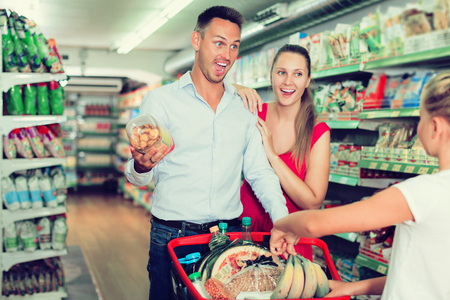 portrait of happy  adult family of three smiling and standing with purchases in shopping mall Stock Photo