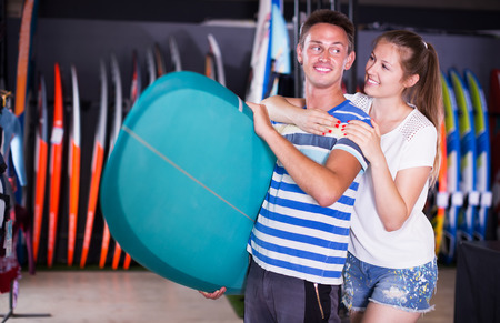 Smiling man with woman demonstraiting new surfboard in store in time summer holidays Stock Photo