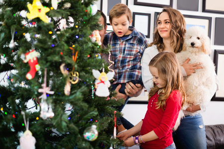 Young pleasant smiling family decorating Christmas tree at home Archivio Fotografico