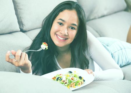 Positive young female eating salad witn fork lying at home