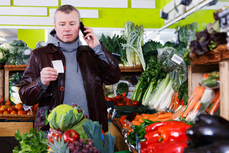 young man looking at shopping list, speaking by phone during purchasing in fruit store Stock Photo