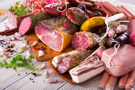 All sorts of sausages, meats and mince with herbs on table