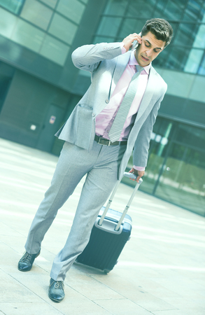 Full-length portrait of traveling businessman walking with bag and talking on phone