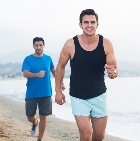 Adult men are jogging together on the beach near ocean. Imagens