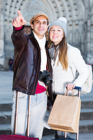 smiling active adult male and female in the historic center pointing finger