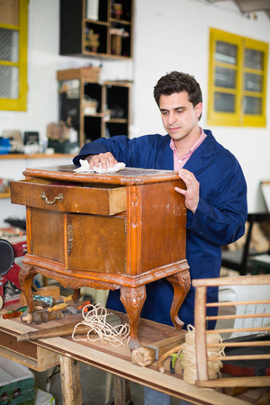 Adult craftsman inspecting old nightstand before restoration in workshop Stock Photo