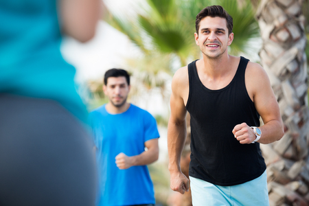 Portrait of adult man who is jogging with friend in the park near ocean.
