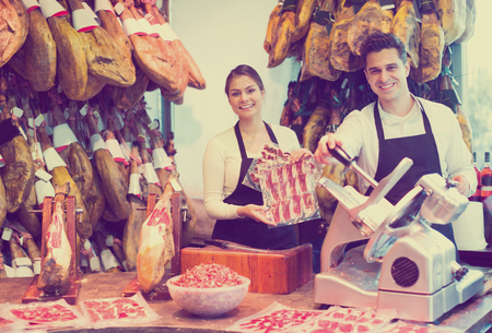 Cheerful sellers offering tasty jamon for customers in shop Stock fotó