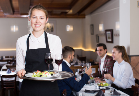 Portrait of smiling waitress with serving tray meeting restaurant guests  Archivio Fotografico