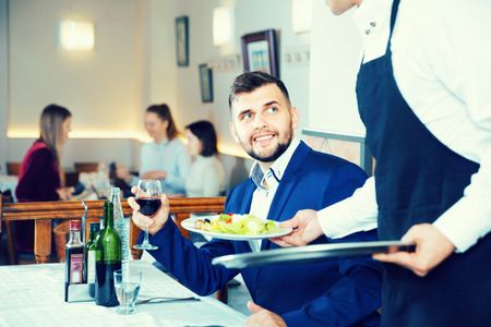 Glad cheerful positive smiling waiter serving delicious salads to handsome young man at restaurant  Stok Fotoğraf