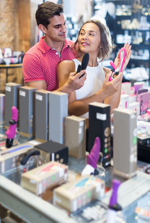 positive european female and male purchasers touching in the modern sex shop different sexy toys   Imagens