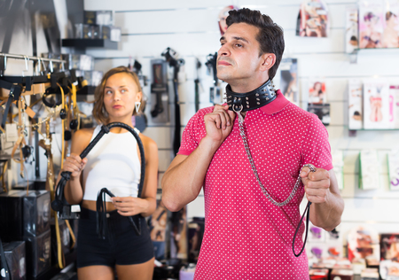 Portrait of joyful girl and man consumers holding collar with thorns and leather whip Stockfoto