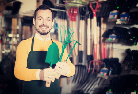 Smiling young man seller displaying various items in garden equipment shop
