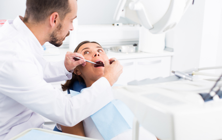 male Dentist is treating patient which is sitting in dental chair in clinic