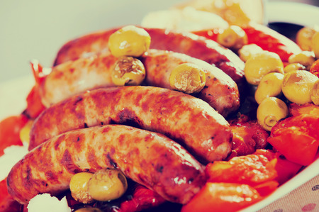 Sausages and vegetables made on grill with cheese and olive oil on table Stock Photo