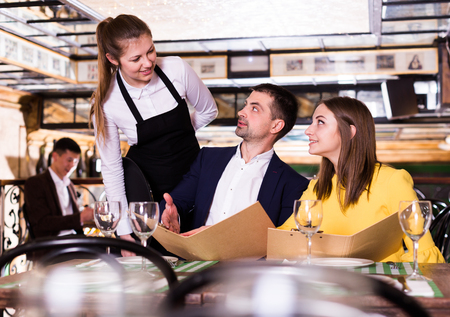 Couple with menu is giving order to woman waiter in time dinner in restaurant.