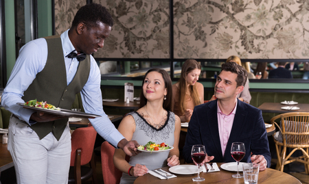 Polite African American waiter bringing ordered dishes to smiling couple at restaurant