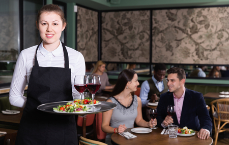 Attractive positive smiling young waitress with serving tray welcoming in restaurant