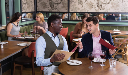 Ð¡heerful  positive smiling male friends choosing dishes from menu card in restaurant