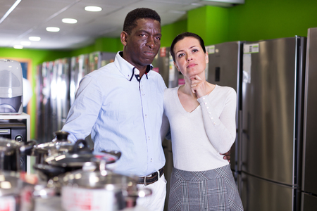 Positive couple standing at a store of household appliances. Focus on woman  Stock Photo