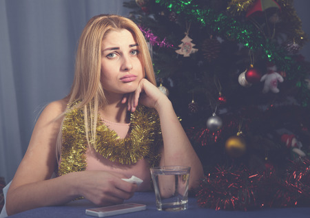 Sad woman is bored with glass of water in New Year night at home.