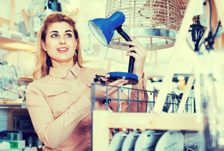 Attractive female housewife buying table lamp in furniture shop Stock Photo