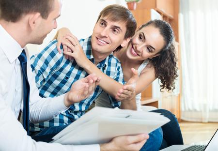 feliz pareja y agente bancario discutiendo posibilidad de hipoteca