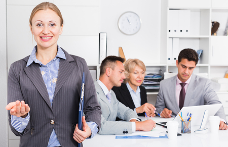 Elegant businesswoman holding clipboard and welcoming to modern office
