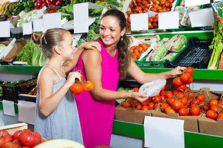 cheerful young woman with daughter buying tomatoes in food store