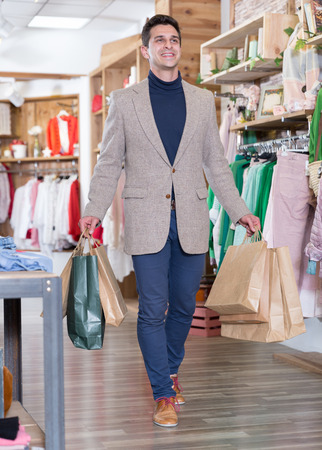 Man is satisfied shopping and walking with package in the clothes store. Stock Photo