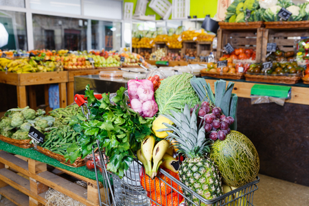 Variety of fresh vegetables and fruits in shopping cart in greengrocery