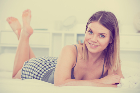 Portrait of young smiling girl lounging in bed in home interior Stockfoto