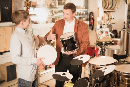 Glad young teenage boy and father choosing best drum unit in musical shop
