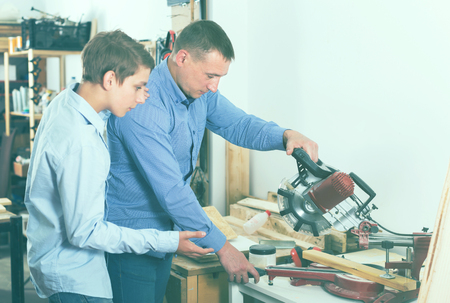 Portrait of woodworker and pupil cutting wooden plank with table saw in workplace