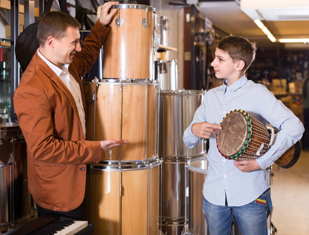positive father and teenage son examining drum units in guitar shop