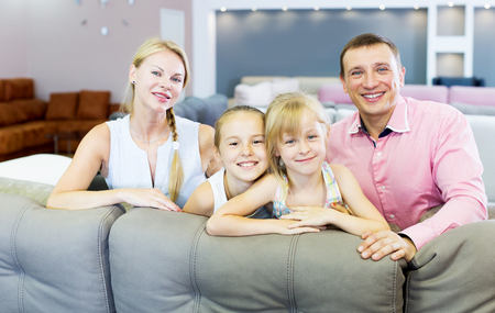 Cheerful young family which is choosing new sofa in the store
