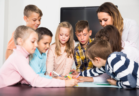 Professor and elementary age children drawing together one picture in classroom Stock Photo