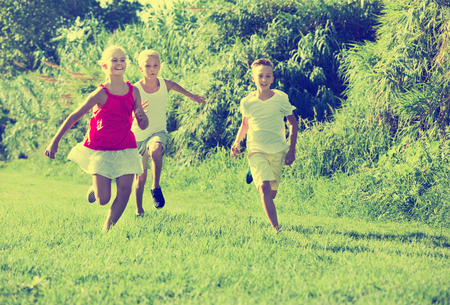 Three positive kids playing active games in summer park chasing each other Reklamní fotografie