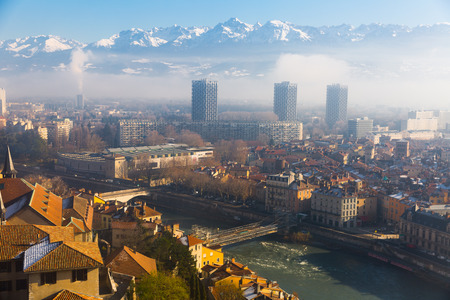 Picturesque mountains landscape of snowy Alps and center of Grenoble under clouds in sunny winter day