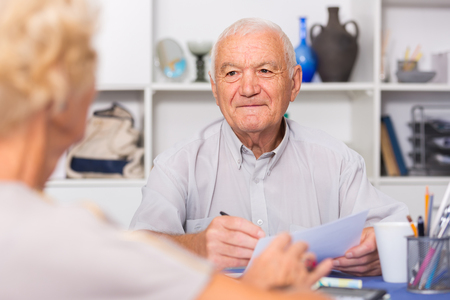 Smiling senior man sitting at home table discussing with wife their bills  Stock Photo
