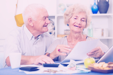 Positive mature couple with papers and laptop at home  Фото со стока