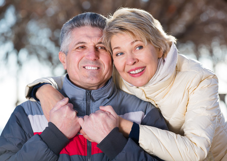Adult husband and wife warmly embracing and resting together outdoors Stock Photo