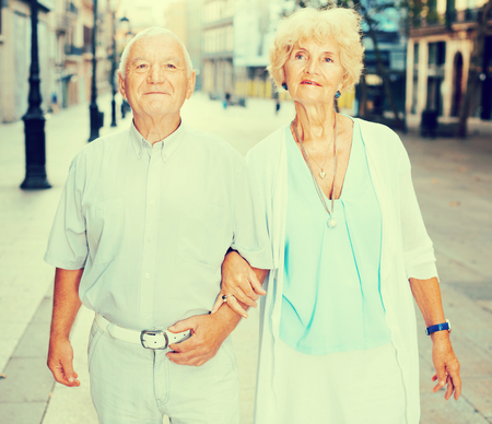 Portrait of positive smiling senior man and woman in love holding hands strolling along city streets Stock Photo
