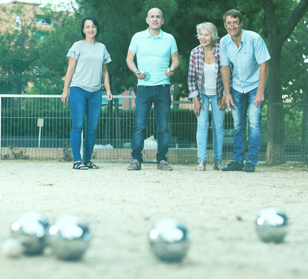 Cheerful males and females playing petanque in th park on holidays