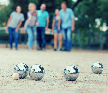 Males and females playing petanque in th park on holidays