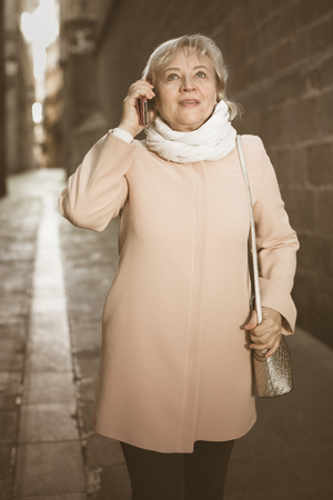 adult woman talking on mobile phone at the historical street Stock Photo