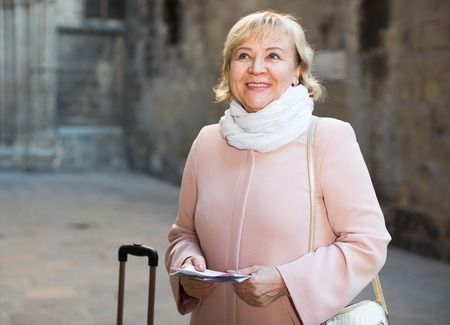 portrait of mature female tourist holding map and baggage Stock Photo