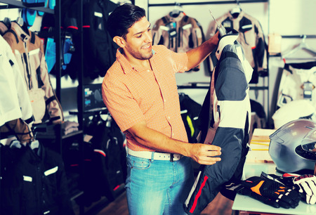 Adult smiling man is choosing jacket-equipment in the moto store Stock Photo