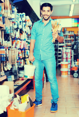 Young cheerful positive smiling man standing amongst racks in paint store with brushes and paint Stock Photo