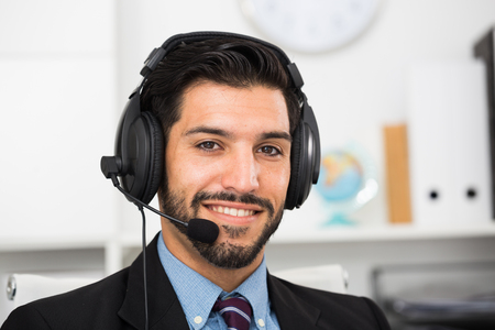 Portrait of spanish man dispatcher who is talking with client in office.